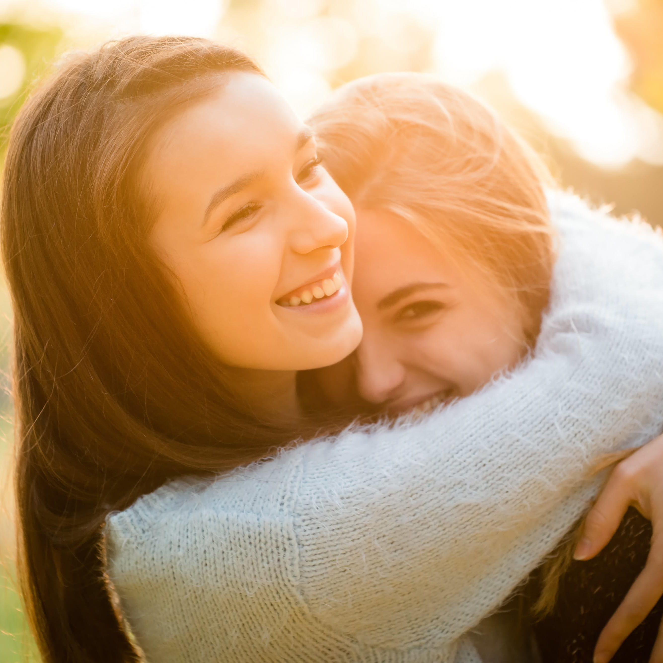 Two friends -  teenage girls hugging  outdoor in autumn at sunset